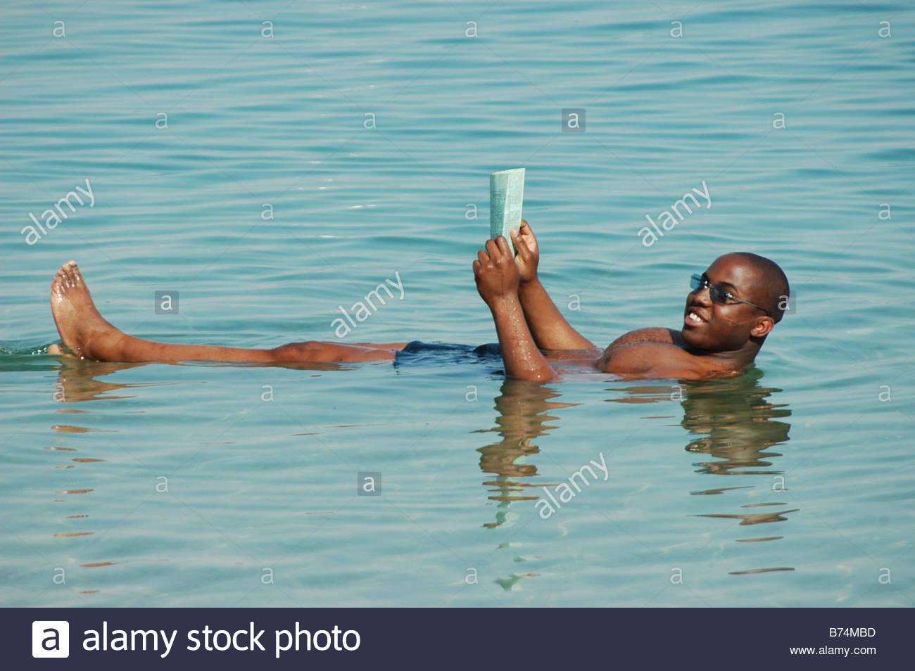 israel-dead-sea-tourist-reeding-newspaper-while-floating-in-the-water-B74MBD.jpg